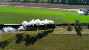 Humo que sopla del tren de pasajeros del vapor a lo largo del campo de Amish según lo visto por un abejón almacen de video