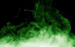 Humo verde en el fondo negro imagenes de archivo