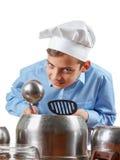 Humor alegre joven del adolescente en el sombrero de un cocinero Él juega los tambores, potes Estudio aislado Imagen de archivo