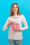 Humor del ` s de la tarjeta del día de San Valentín Corazón de papel en las manos Muchacha sonriente agradable en blanco Imágenes de archivo libres de regalías