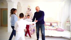 Humor do ` s do ano novo da família feliz e do passatempo do divertimento junto no quarto com a árvore de Natal no dia filme