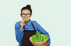 Humor feliz vegetal verde comer asiático da menina imagem de stock