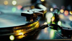 Humor festivo, luces del bokeh que brillan sobre cierre de la aguja del tocadiscos de la placa giratoria del vinilo del vintage e almacen de video