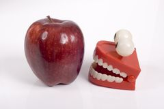 Humor la foto de la manzana roja y los dientes falsos del juguete con los ojos Foto de archivo