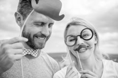 Humor and laugh concept. Couple posing with party props sky background. Photo booth props. Man with beard and woman royalty free stock photography