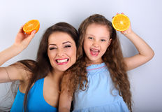 Humor laughing young mother and cute long hair daughter holding Stock Photos