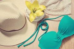 Humor para las vacaciones o viaje - sombrero de paja, traje de baño, bufanda y flor amarilla en un fondo de madera Endecha plana  Imagen de archivo