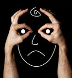 Humor triste y cara infeliz con las manos en fondo negro Imágenes de archivo libres de regalías