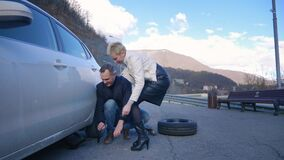 Humor. woman changing a car wheel. a man rides past on electric skate Board. stock video