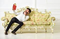 Humoristisch literatuurconcept Kerel die oud boek met plezier lezen Macho op het lachen het boek van de gezichtslezing Mens met b stock foto
