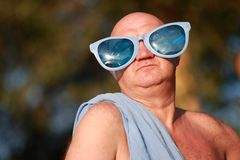 Humoristisch portret van een volwassen kale mens in een blauwe toga en grappige blauwe glazen stock foto