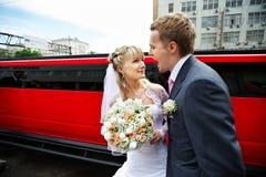 Humoristische beeldbruid en bruidegom op rode limo Royalty-vrije Stock Foto's