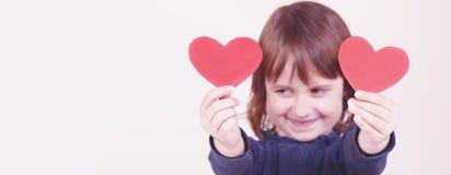 Humoristische foto van leuk weinig kindmeisje met harten op de ogen als symbool van liefde en amorousness Selectieve nadruk op ha stock foto's