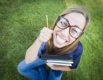 Humoristisk bred vinkel av nätt tonårigt med böcker och blyertspennan Fotografering för Bildbyråer