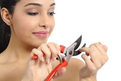 Humorous beautiful woman making manicure with a secateurs. Isolated on a white background Stock Photography