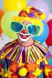 Humorous Birthday Clown. Funny birthday clown wearing over-sized novelty sunglasses royalty free stock photo
