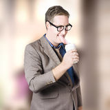 Humorous businessman licking top of coffee cup Royalty Free Stock Photo
