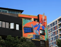 Humorous colorful mural, Wellington, New Zealand. Modern orange mural of man in red sport jacket and jean and sneakers Stock Images