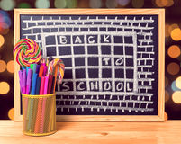 Humorous concept of hate school as prison with text back to scho. Ol is written in chalkboard, pen holder, peppermint candy on wooden table over blur background Stock Images