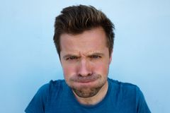 Humorous emotional portrait of grimacing young man Stock Image