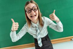 Humorous high angle view of Happy young schoolgirl has her thumbs up Stock Photography