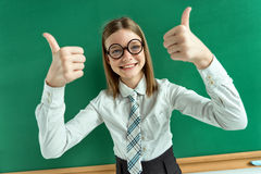 Humorous high angle view of Happy young schoolgirl has her thumbs up Royalty Free Stock Photography