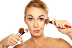 Humorous image of woman with makeup brushes Stock Photography