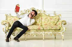 Humorous literature concept. Guy reading old book with enjoyment. Macho on laughing face reading book. Man with beard. And mustache sits on baroque style sofa Stock Photo