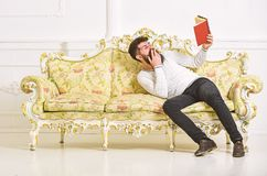 Humorous literature concept. Guy reading old book with enjoyment. Macho on laughing face reading book. Man with beard. And mustache sits on baroque style sofa royalty free stock image