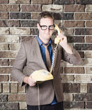 Humorous male nerd chatting business on phone Stock Image