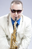 Humorous Male Saxophone Player Performing On Alto Saxo In White Suit and Sunglasses Stock Image