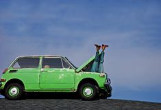 Humorous Manequin Legs Sticking Out of Car. This humorous photo depicts a woman's manequin legs sticking out of the hood of a small green car's hood against Royalty Free Stock Photos