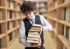 Humorous nerd professor with many books in library.  royalty free stock images