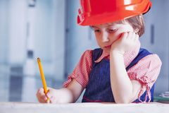 Humorous photo. Cute little child girl engineer in construction. Helmet working with document and blueprints in office Stock Photo