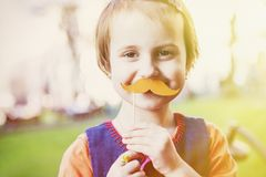 Humorous photo. Cute little child girl holding fake paper mustac. Hes Stock Photo