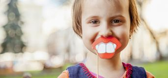 Humorous photo. Funny beautiful little child girl playing with f. Ake lips and teeth Royalty Free Stock Images