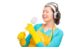 Humorous photo housewife with headphones and a cleaning brush Royalty Free Stock Photography