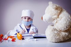 Humorous photo. Little cute child girl playing doctor fills up t. He prescription form to the patient. Prescribe treatment, health concept Royalty Free Stock Photo