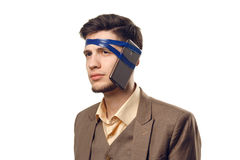 A humorous photo of modern technologies. Young guy with a phone attached to the head using a tape. Uncut on white Royalty Free Stock Images