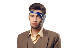 A humorous photo of modern technologies. Young guy with a phone attached to the head using a tape. Uncut on white Stock Images