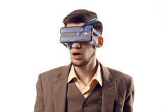 A humorous photo of modern technologies. Young guy with a phone attached to the head using a tape. Virtual reality gadget. Cut out on white Royalty Free Stock Images