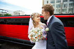 Humorous picture bride and groom on red limo Royalty Free Stock Photos