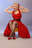 Humorous pinup girl in red dress with tattoo. Amazed, shocked or delighted humorous pin-up pose Royalty Free Stock Photography