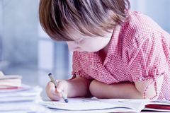 Humorous portrait of child girl artist designer draws a pencil s. Ketch. Close up Royalty Free Stock Images