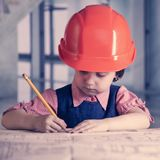 Humorous portrait of cute little child girl engineer in construc. Tion helmet working with document and blueprints in office Stock Photography