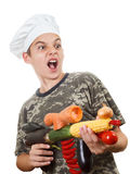 Humorous portrait of a teen boy chef with rifle vegetables, screaming cheers. Humorous portrait of a teen boy chef with opened mouth and rifle vegetables Royalty Free Stock Images