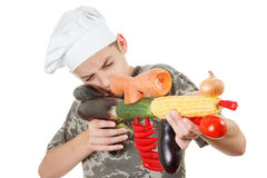Humorous portrait of a teen boy chef with rifle vegetables, white background Stock Photo