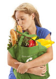 Humorous portrait of young woman kissing food. Humorous portrait of young woman with green recycled grocery bag kissing food Royalty Free Stock Photo