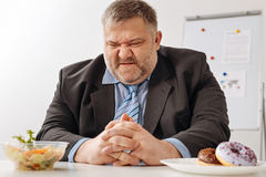 Humorous pudgy employee unhappy about his new diet stock photo