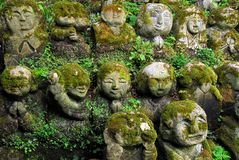 Humorous rakan. Stone rakan , Buddha statues with funny humorous faces partially covered by greenery Royalty Free Stock Images